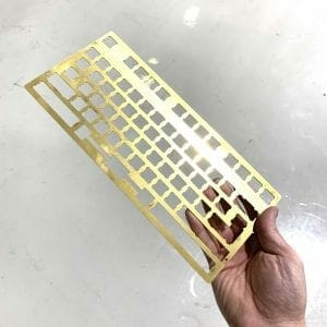 A brass keyboard base being held up